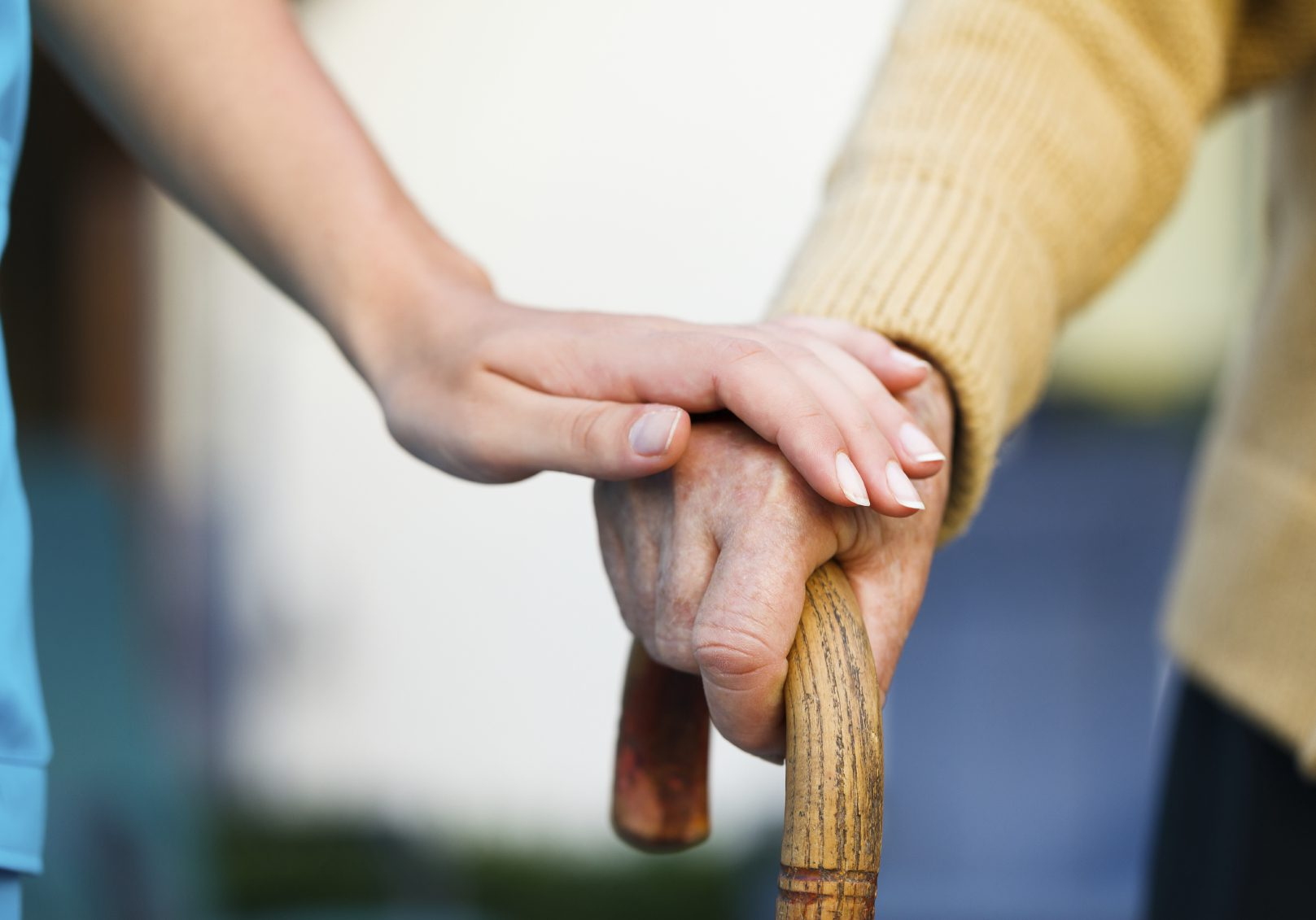 Doctor holding a senior patiens 's hand on a walking stick - special medical care concept for Alzheimer 's syndrome.